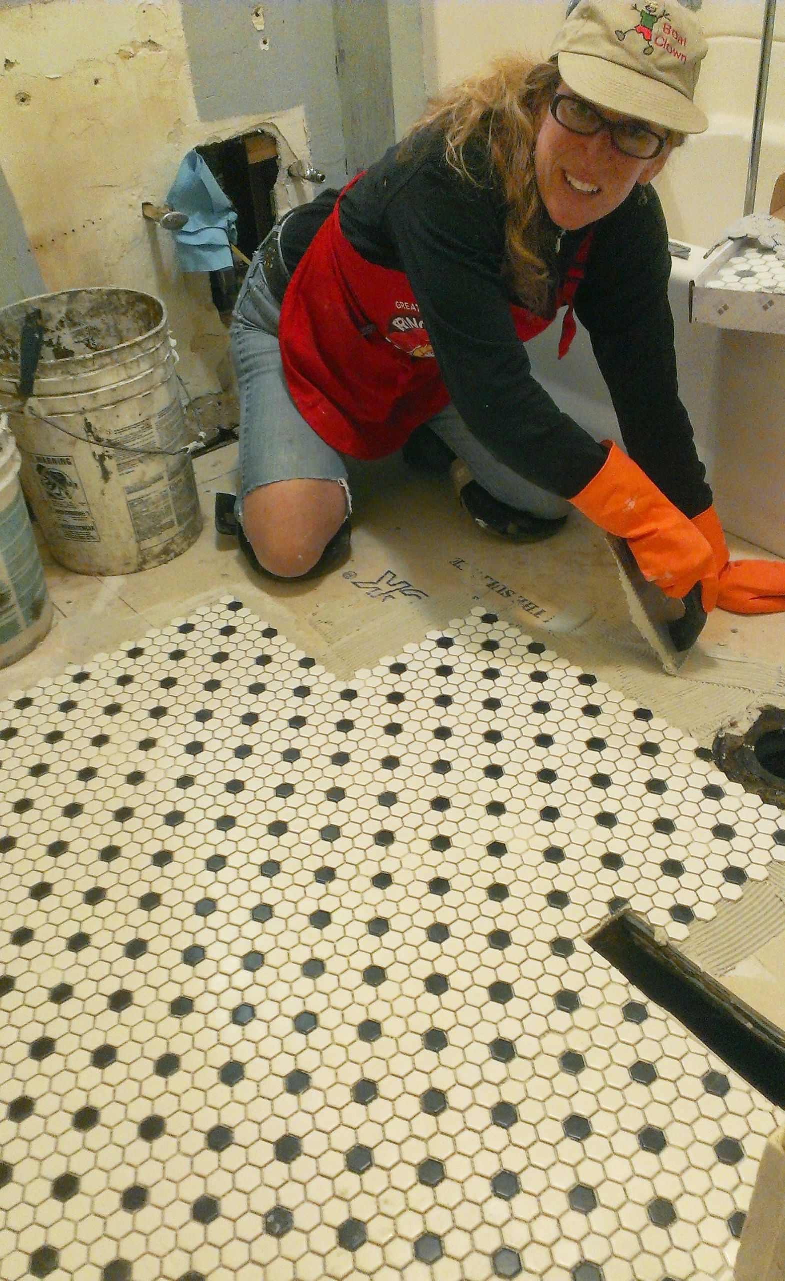 Michele installing 1x1 black and white hex tile mosaics on bathroom floor.